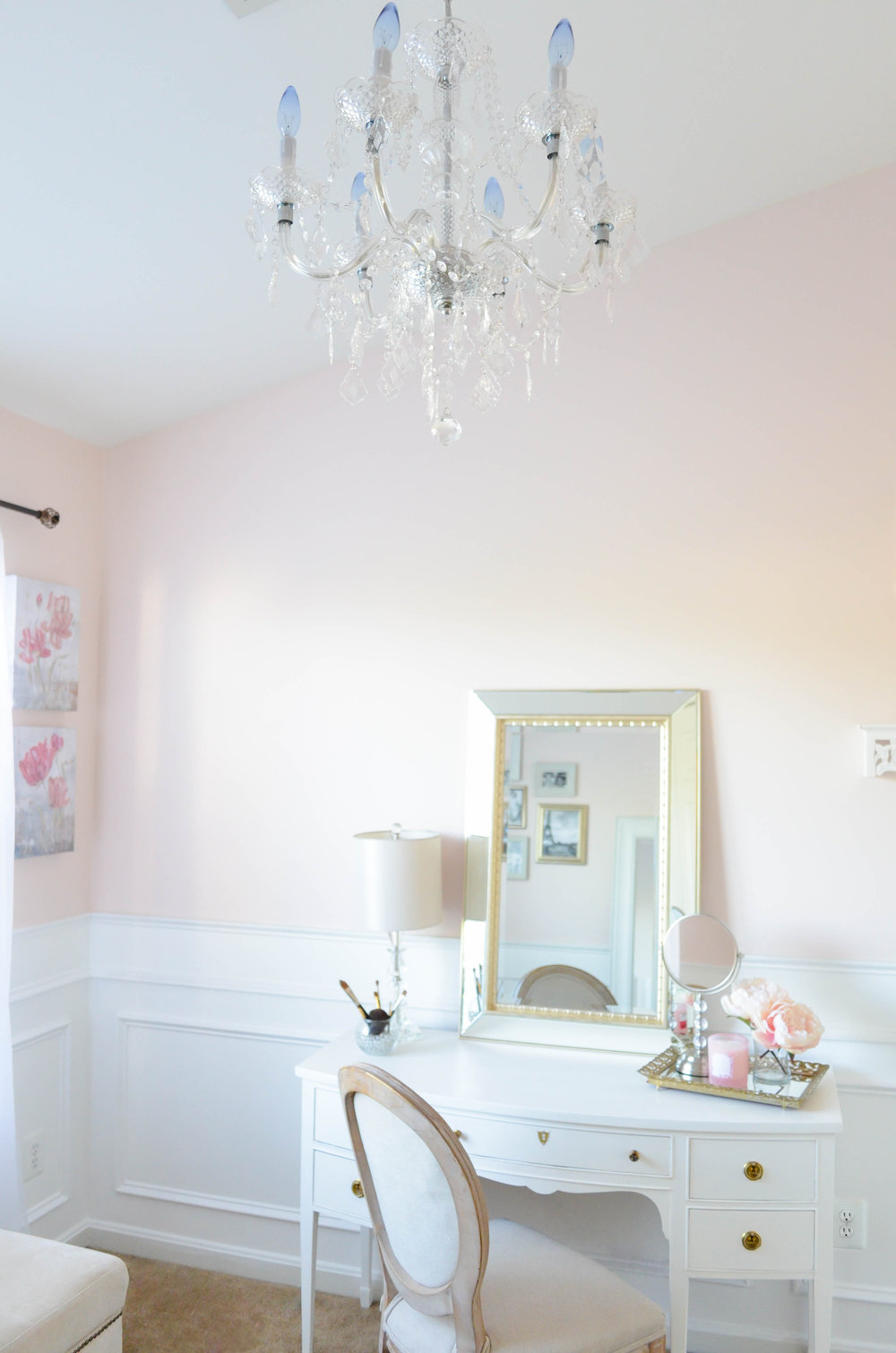 This elegant Parisian inspired Beauty Room is the perfect retreat for the lady of the house to escape with a glass of wine or a pot of tea. The impeccable white wainscoting compliments the soft pink walls and Parisian style decor. A perfectly placed white vanity makeup table adorned with a soft gold beveled mirror is the perfect place to apply those finishing touches for a night out on the town!