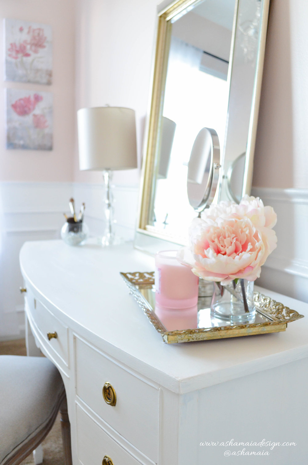 Intimate White Parisian Style Elegant Beauty Room with White Wainscoting, Picture Frame Wall Gallery, White Traditional Makeup Vanity with King Louis Chair and Peonies in Vase