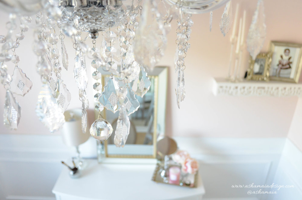 Intimate White Parisian Style Elegant Beauty Room with Crystal Chandelier, White Wainscoting, White Traditional Makeup Vanity with King Louis Chair, Gilded Mirror and Peonies in Vase