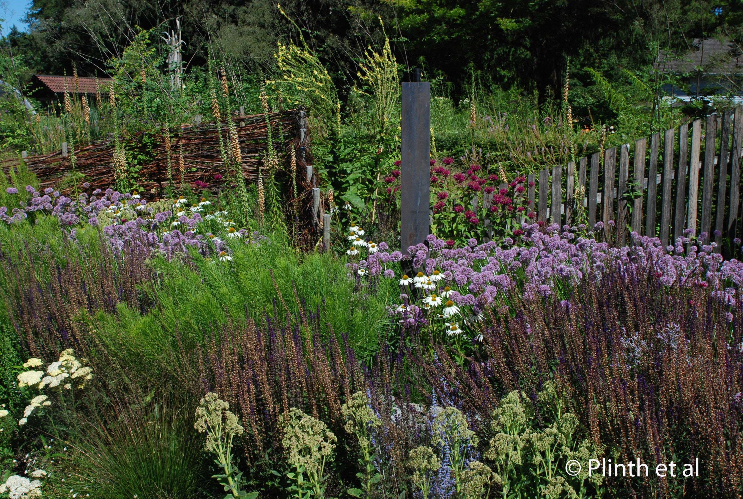 Rustic structures (wattle fence, stone plinth, and zig-zag wood pathway) are skillfully used in harmony with the herbaceous planting, an understated approach that is the signature  mark of the Vrijmoeds.