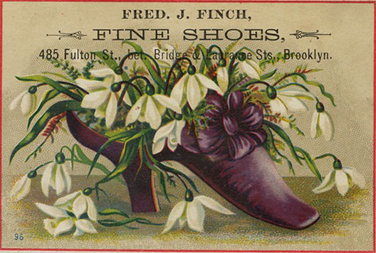 An old advertisement shows snowdrops stuffed into a high-heeled purple women's shoe.