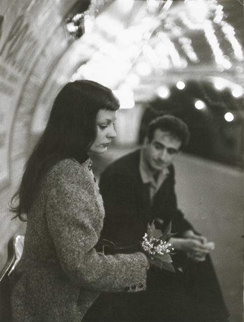 """Robert Doisneau's """"Le Muguet du Métro"""" (Marc and Christiane Chevalier in the Paris Metro) - The woman averts her gaze away from the expectant man on the muguet, which appear remarkably fragile in the hard carapace of the Paris Metro. With his hands clasped and eyes downcast, the man seemingly awaits the woman's reaction as if apologetic for an unspoken wrongdoing."""