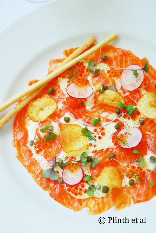 An edible study in orange: Salmon carpaccio with salmon roe, radish, and potato chips with breadsticks