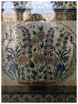 Figure 2: An inlay design of colored glass from the City Palace in Udaipur, Rajasthan, this piece features four of the most canonical flowers of seventeenth- and eighteenth-century South Asian art: poppies and larkspur, combined as is so often the case, Tazetta narcissi, and irises. The Udaipur-based Rajput royal family of Mewar had a complicated relationship to the Mughal Empire, to some degree resisting the accommodation under its suzerainty and absorption into Mughal military and administrative service that was the fate of other local ruling lineages. Nonetheless, it shared actively in its material and artistic and its taste in flowers and floral ornament. Photograph by author.