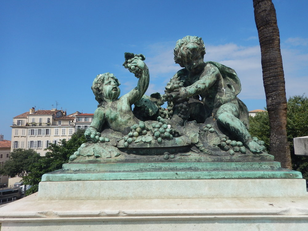 the French have a long history of producing fine wines. This sculpture is in Marseille, at the railway station, with coastline in distance.