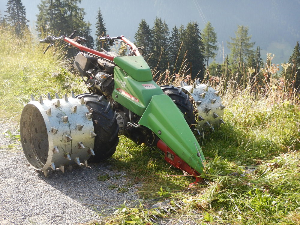 this is the walk-behind reciprocating mower and heavy duty spiked wheels they use to mow fields on steep slopes.