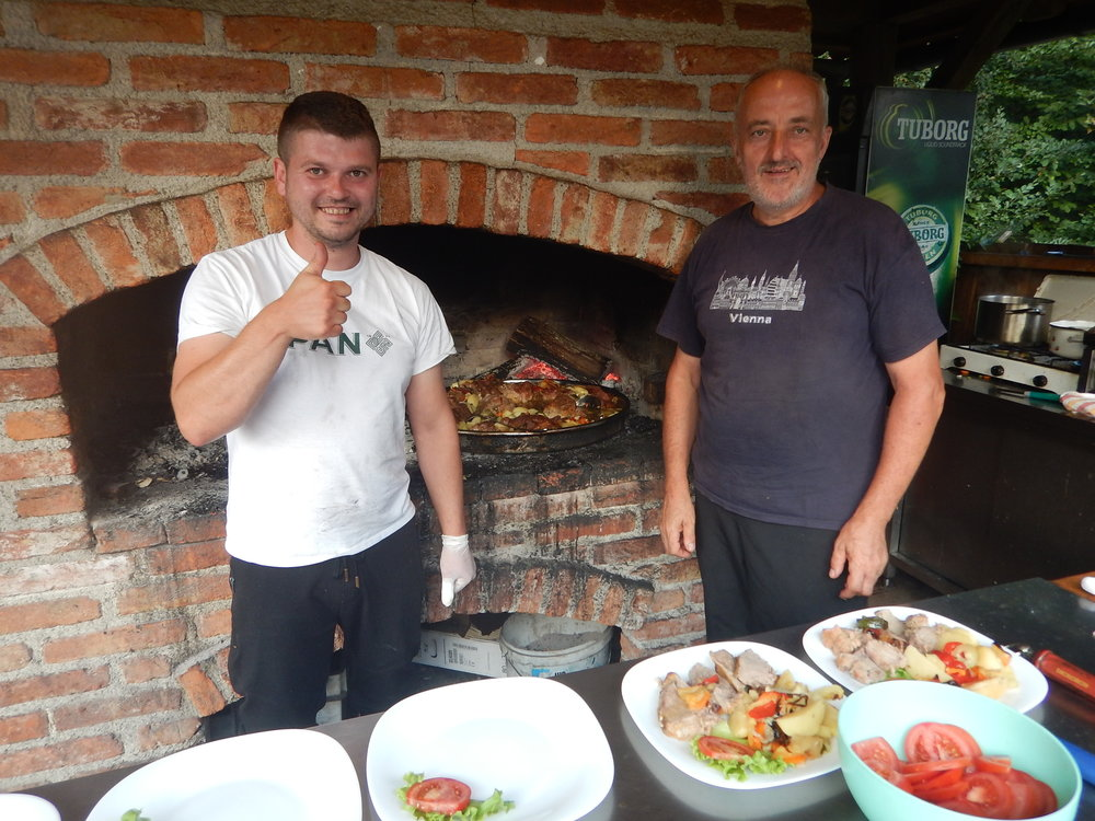 Father and son team in their restaurant kitchen. Meat and veg casserole ready to serve