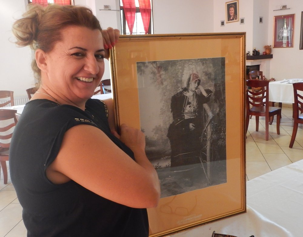 The hotel manager with one of the historical photos decorating the hotel.