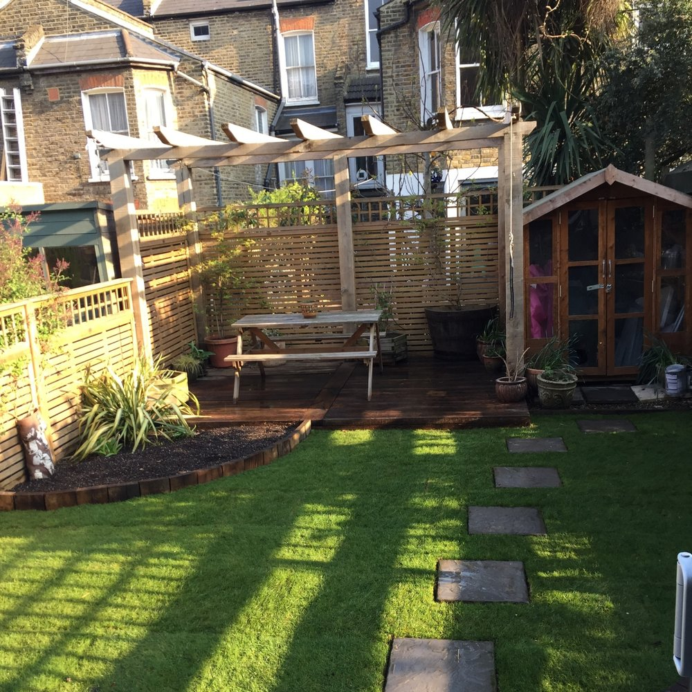 Clapton  small rear garden in Clapton: bespoke deck and pergola constructed at the rear of the garden using freshly sawn oak with some substantial timber uprights. Along with some blue slate paving adjacent to the house, a small lawn bordered with two diagonal planting beds and some high quality Venetian facing and trellis was installed surrounding the garden.