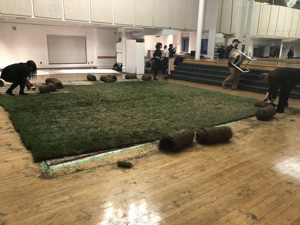 Volunteers clearing the sod off the floor after the performance (Photo by: Chloe Cook)