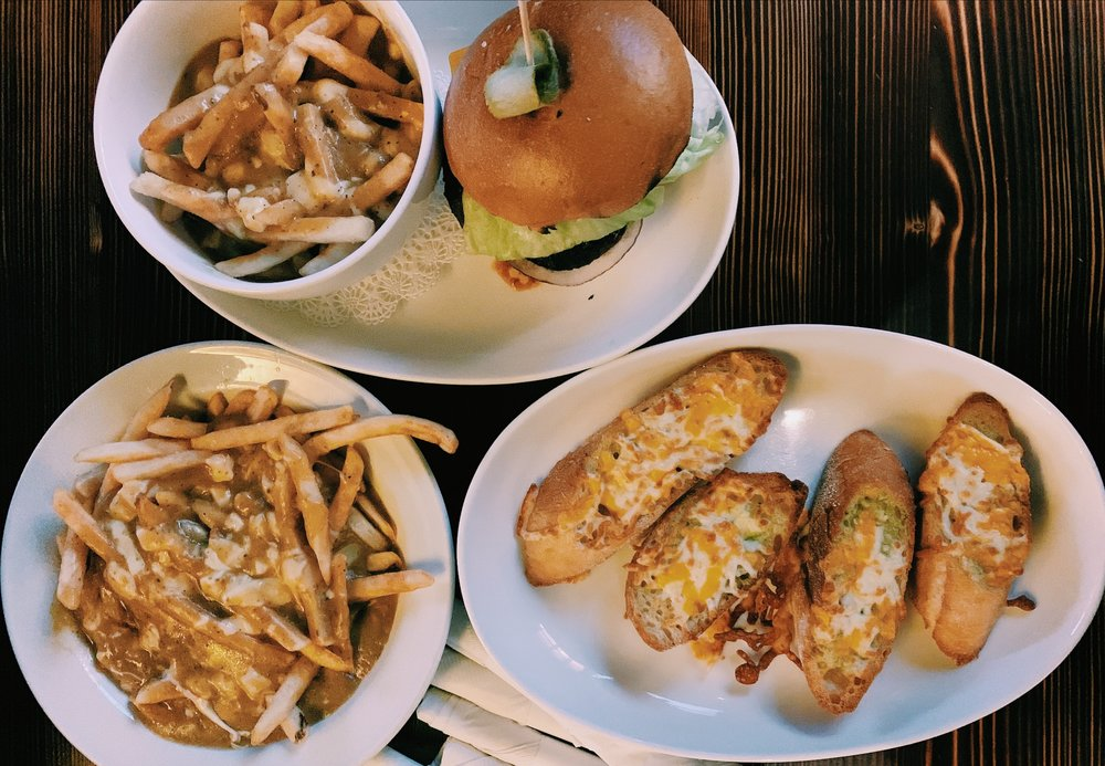 A cheeseburger, poutine, and garlic bread from Ram in the Rye. (CanCulture/Akanksha Dhingra)
