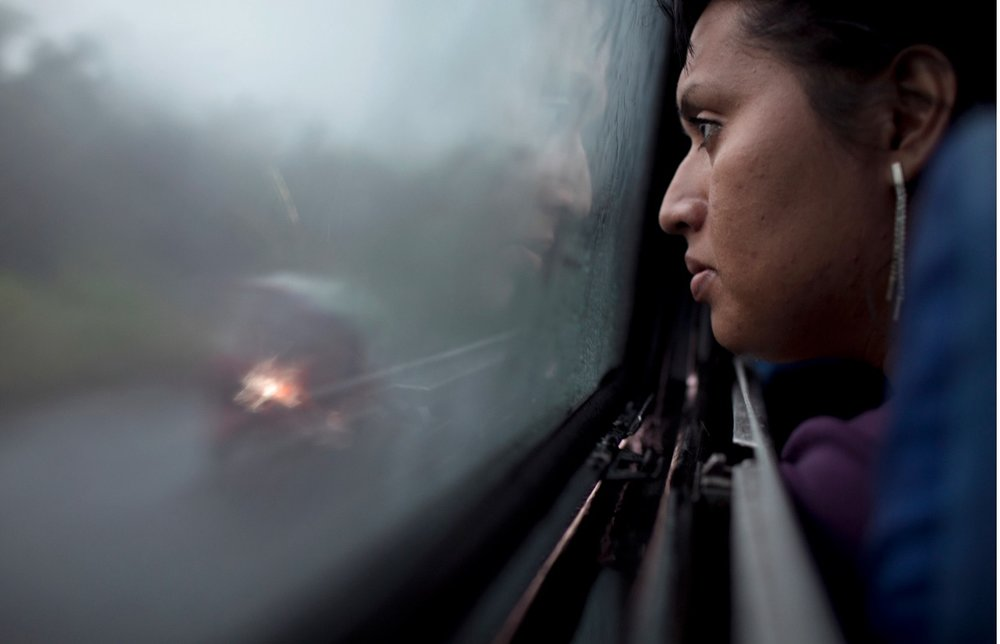 As dawn arrives, Marfil Estrella looks out the window of the bus that will take her from San Salvador, El Salvador to Guatemala City, Guatemala. Photos by  Danielle Villasana .