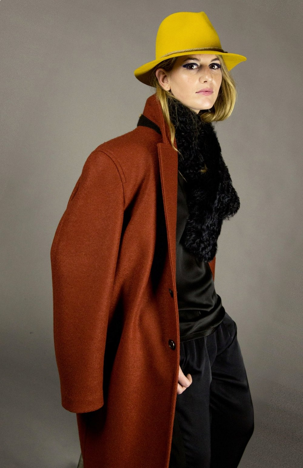 COAT 1 RUST  2-button walking coat.oversized fit. drop shoulder. unlined with bias piped seams. natural melange rope detail at neck.natural horn buttons. below knee length.  sizes 0-1-2-3  100% italian boiled-wool jersey  also available in black