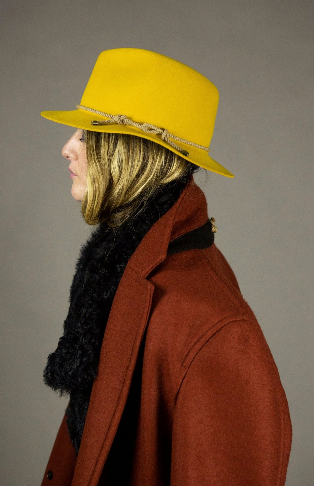 hat 1 gold  felted fedora with signature natural melange rope detail and brass metal tips. made in collaboration with bollman hats, the oldest hat manufacturer in america.  sizes 1-2  100% felted wool  100% cotton interior band in our signature khaki twill