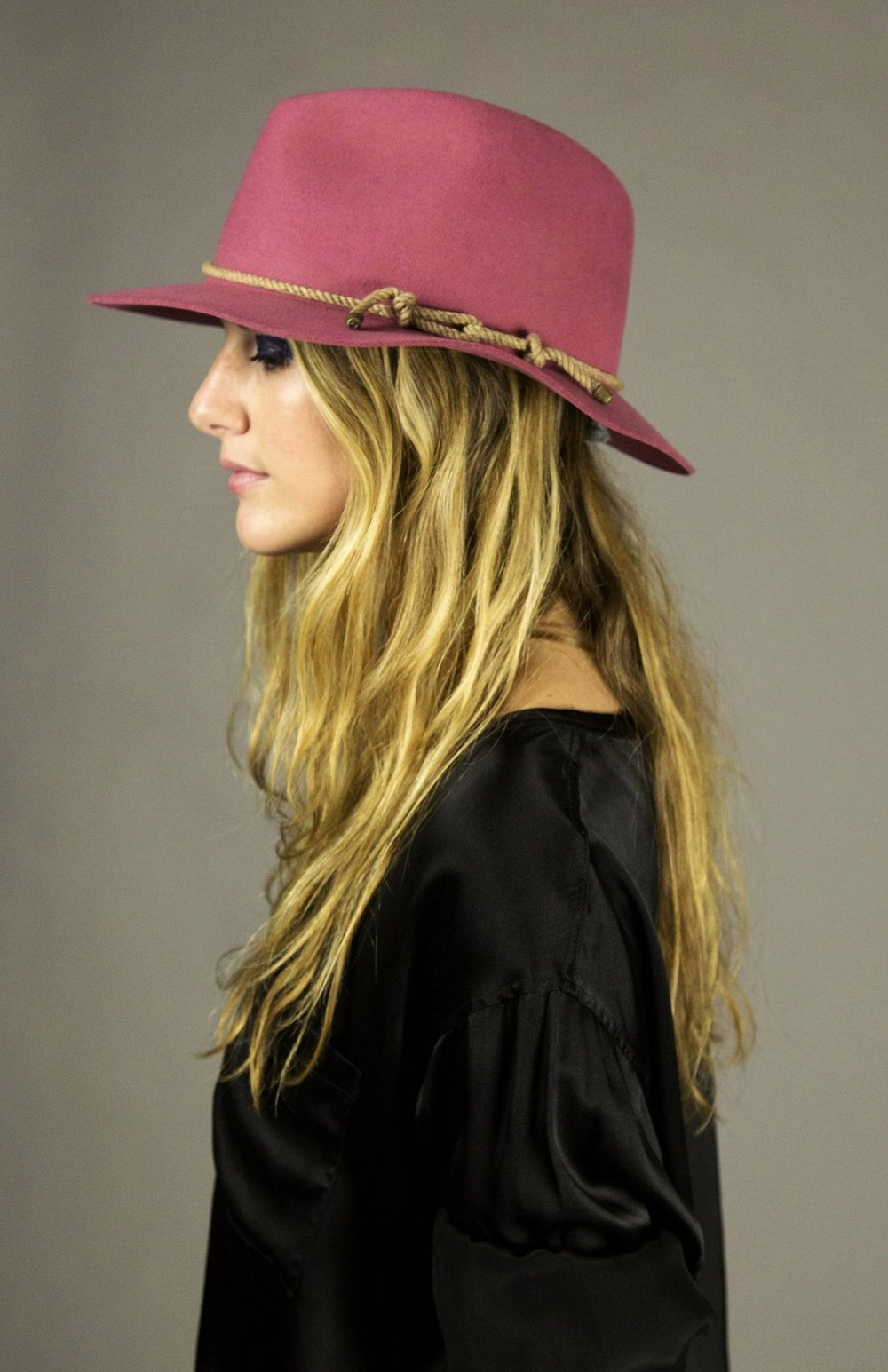 hat 1 pink  felted fedora with signature natural melange rope detail and brass metal tips. made in collaboration with bollman hats, the oldest hat manufacturer in america.  sizes 1-2  100% felted wool  100% cotton interior band in our signature khaki twill