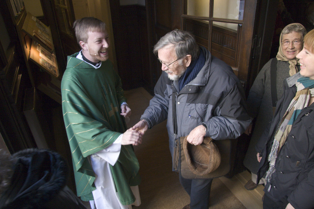 Daniel Nørgaard shakes hands with parishioners at the doors of Sankt Ansgar's Cathedralin Copenhagen.