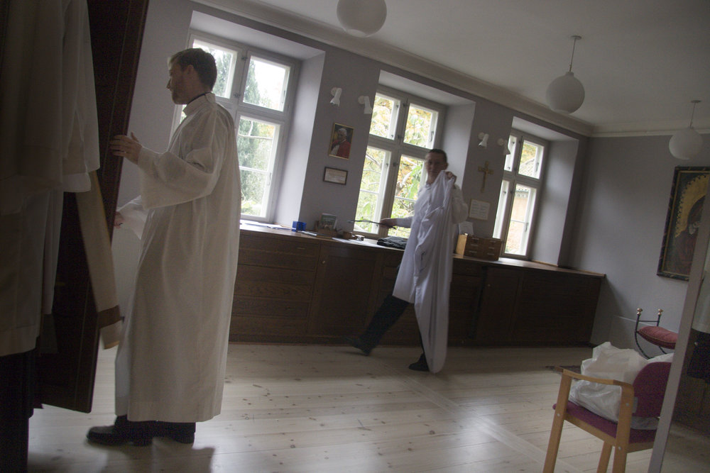 Daniel Nørgaard, left, puts on his robes before mass at Sankt Ansgar's Cathedral in Copenhagen.