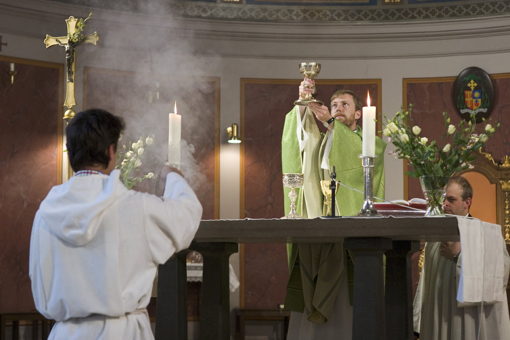 Father Daniel Nørgaard lifts the communion cup during mass at Sankt Ansgar in Copenhagen, Denmark