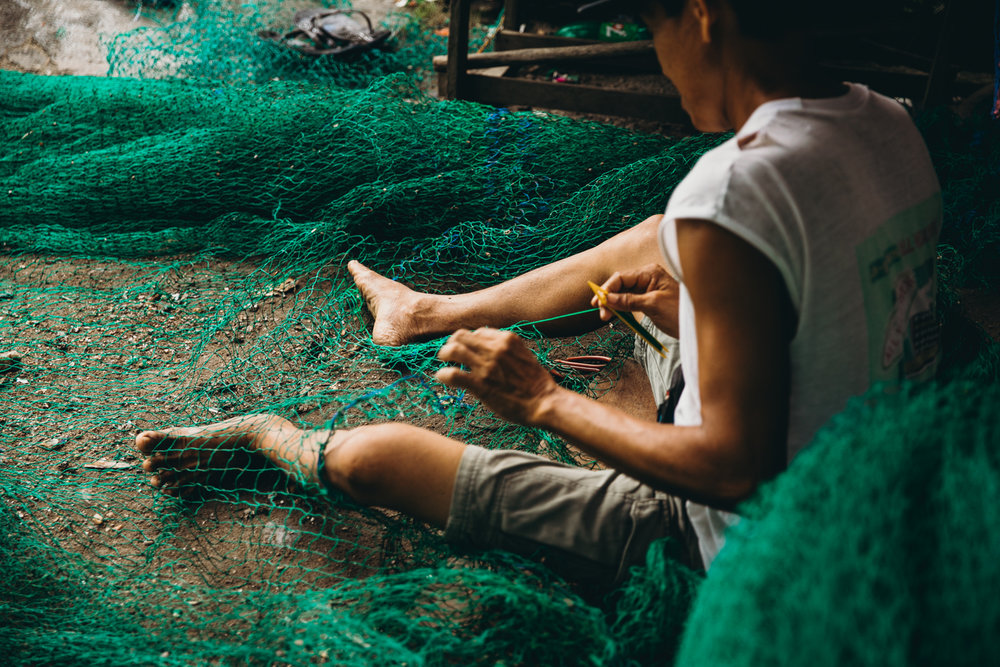 A fisherman repairing his net in the Philippines.