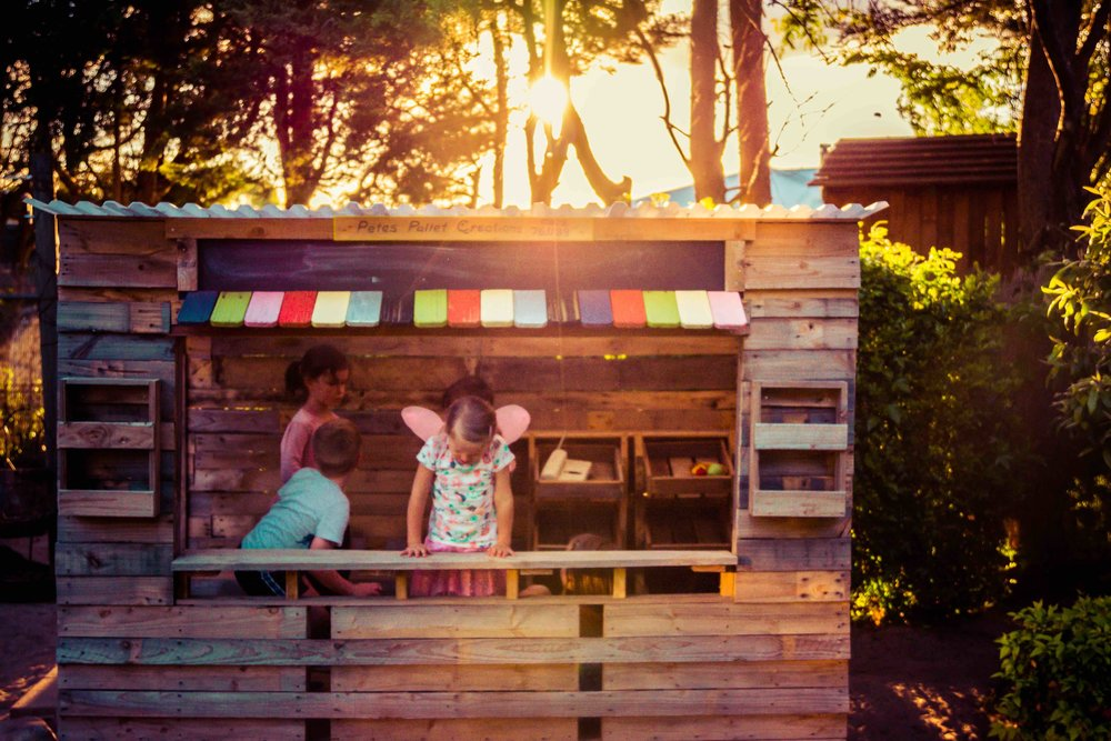 Chiselhurst Kindergarten children playing in the outside shop made out of wooden pallets.