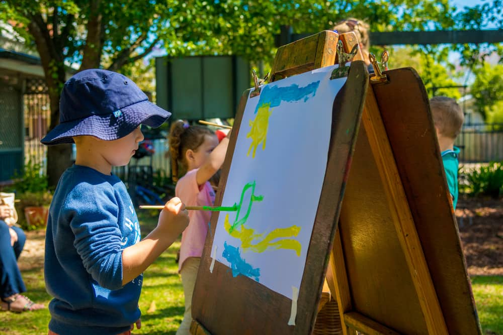 Boy painting on old wooden easel in Chiselhursts front garden