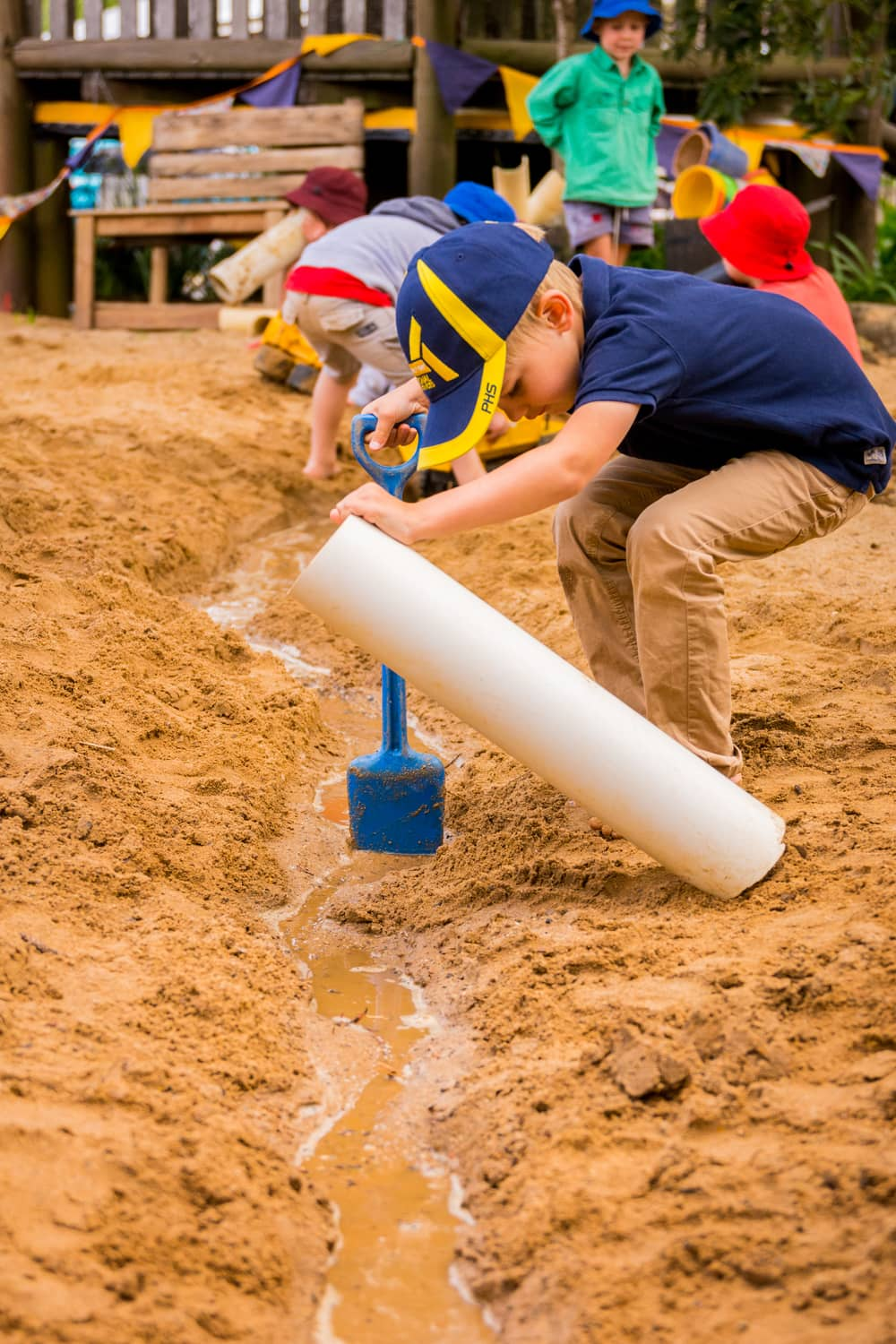 Children playing in kindy sandpit with spades and white pipe