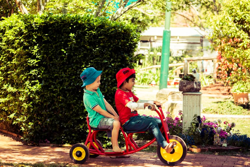 Boy giving his friend a ride on a red tricycle