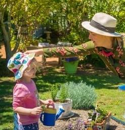 Educator helping keep little girls hat on while tending the Chiselhurst vegetable garden