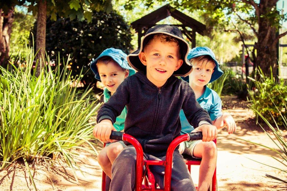 Three boys on red tricycle in Chiselhurst Kindergarten garden