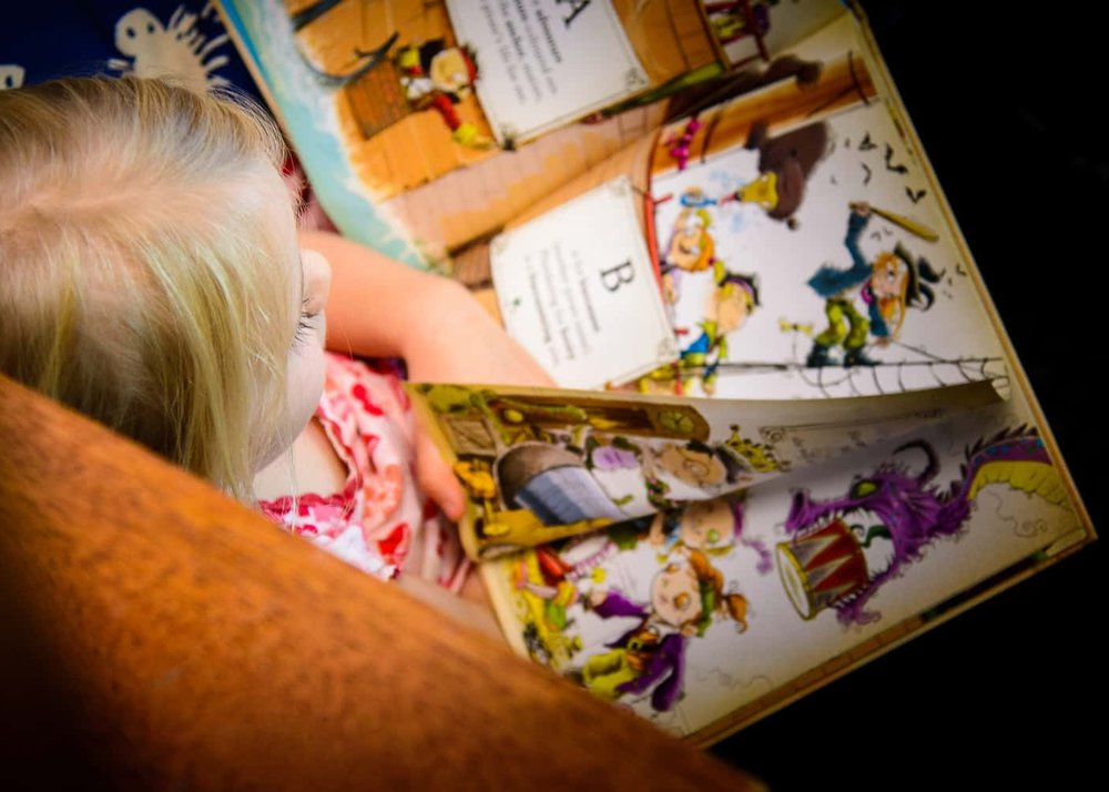 Chiselhurst girl reading a beautiful picture book from the kindergarten library