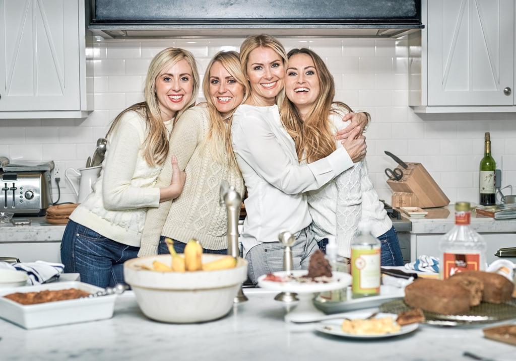 Portrait of the four FOOD NANNY sisters showing sister love while standing in the kitchen. Liz, Emaly, Katey, Aimee