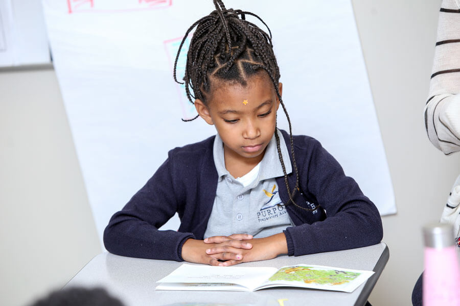 A girl sitting in her classroom, concentrating on her reading assignment