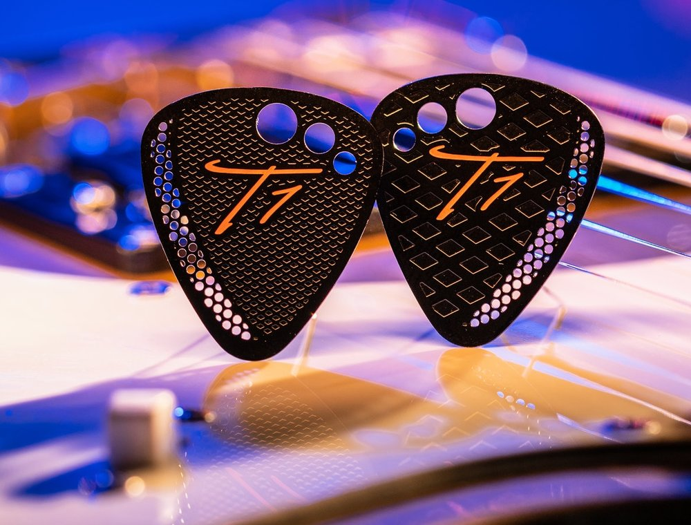 "Keeping it Classy! T1's ""Guitar"" Pick is the standard guitar pick shape you are use to. Keeping with all the same T1 pick design features. T1 ""Guitar"" Picks are hit with a coat of paint for that flat black finish, then hit with a Orange screen printed logo. T1 picks feel and sound better with use. Due to the painted process, you may find the paint start to scratch off the tip. This is normal, it looks pretty sweet too!"