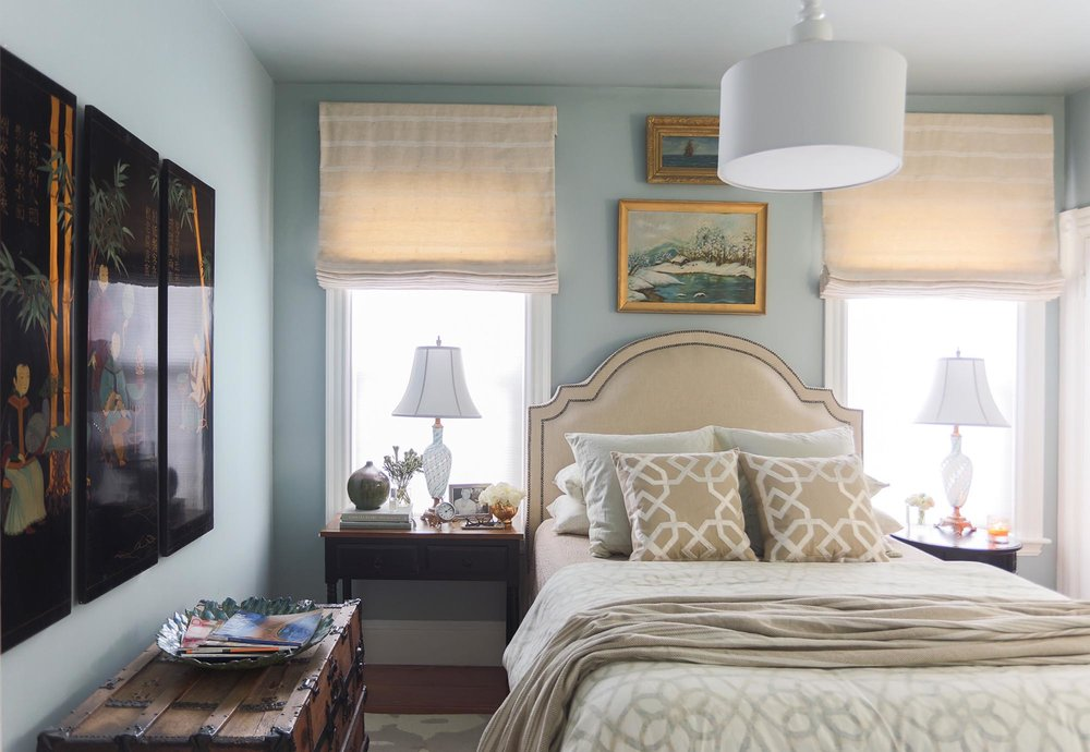 Light painted bedroom with double size bed, two lamp shades and white ceiling lamp.