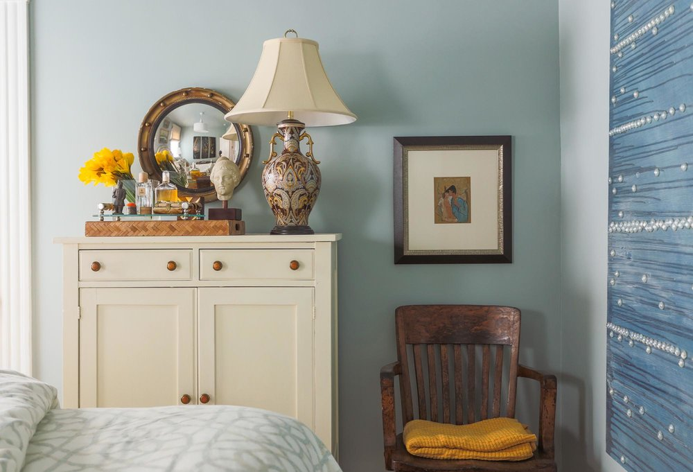 Bedroom interior with single hair, lamp shade and other decorations on the top of the white wooden dresser.