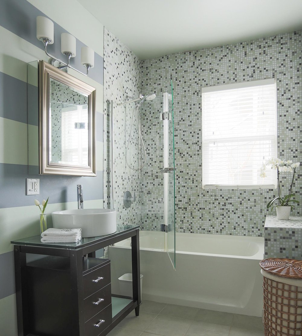 Bathroom Design with Striped Painted wall and white bath tub with glass window.