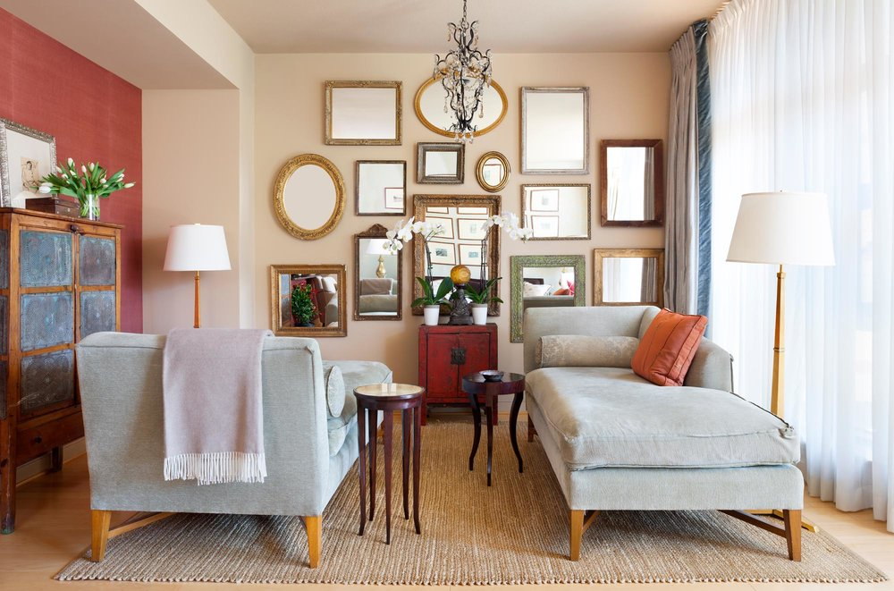 Living Room Design with different mirror designs hanging on the wall, two large sofa day bed and floor lamps
