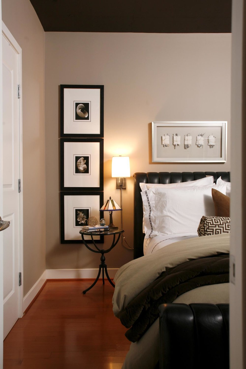 Condo Bedroom Design with frames hanged on light painted wall and stylish lights