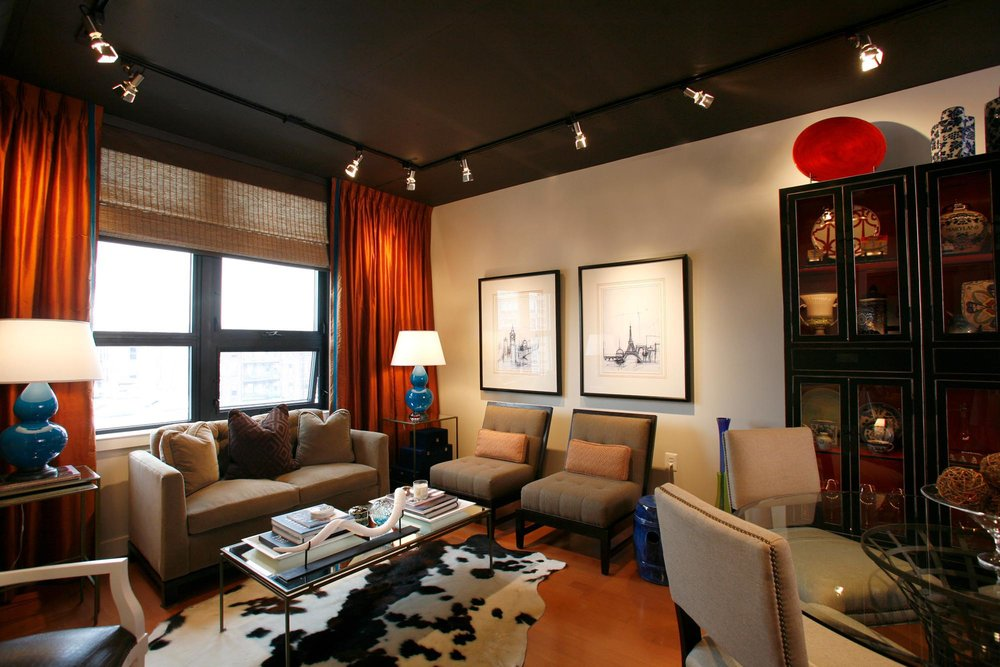 Condo Living Room Design with black and white design rug, light brown sofa and mini lights on the ceiling