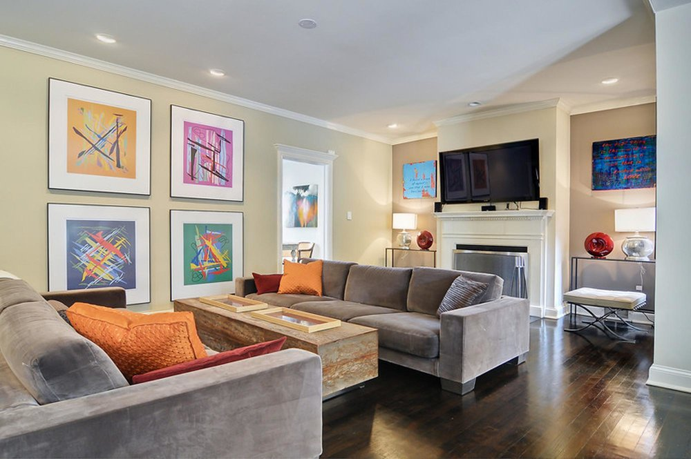 Living Room Design with large brown sofa set, television set and paintings on the wall