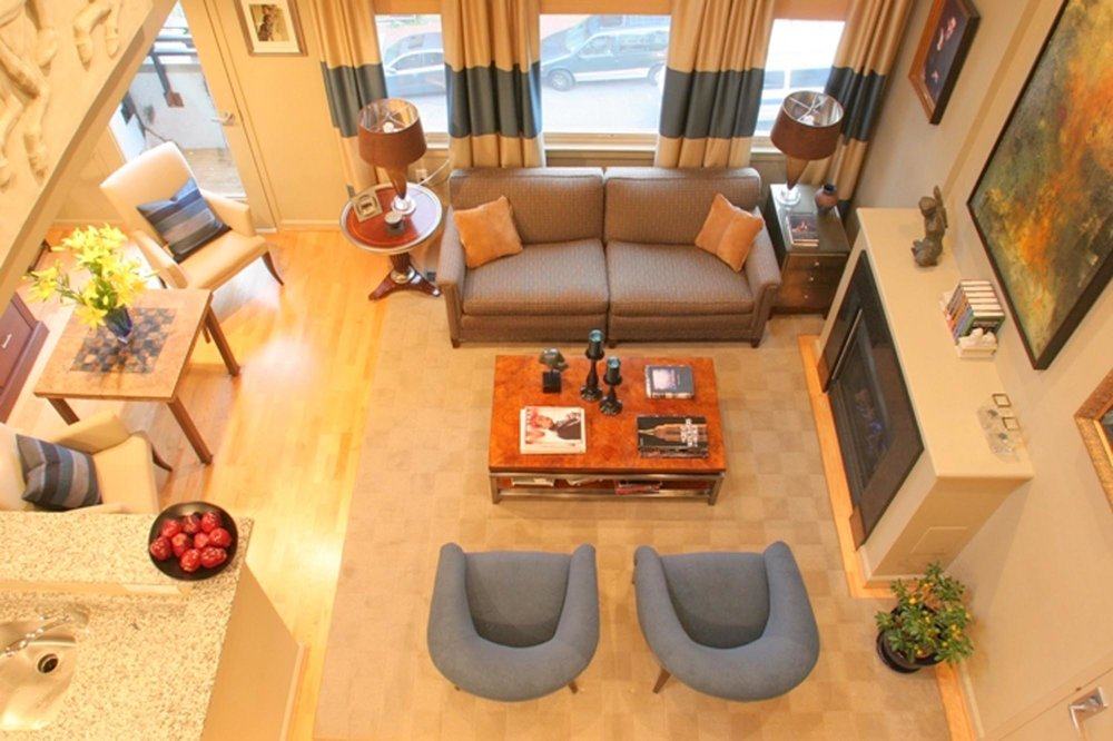 Top view of the modern living room interior with sofa and arm chairs, fireplace and other decorations