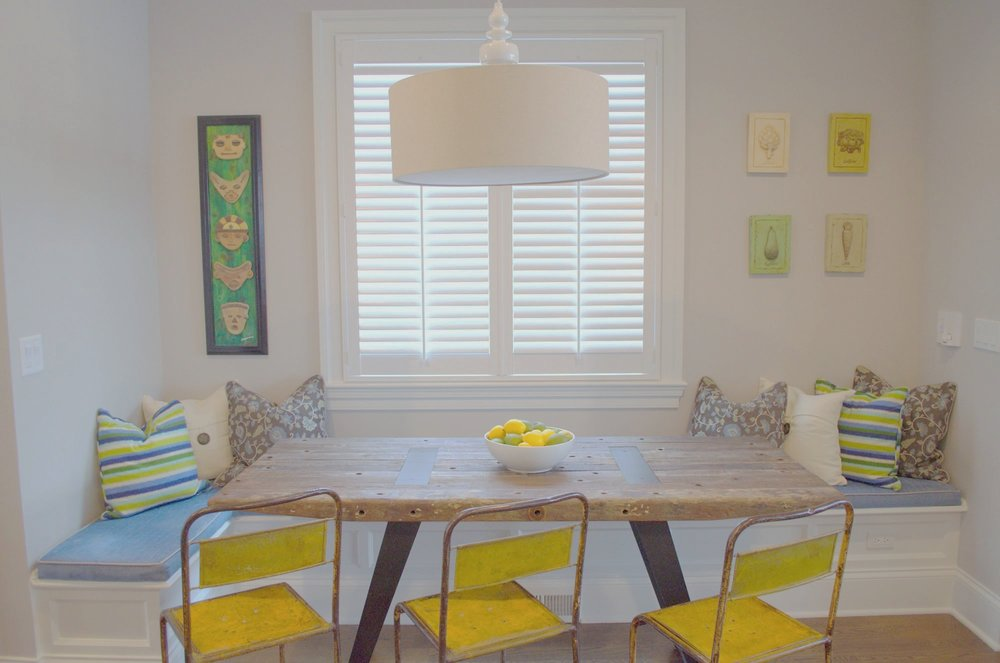 Dining area with dining table for three and storage bench with stylish pillows on walls.
