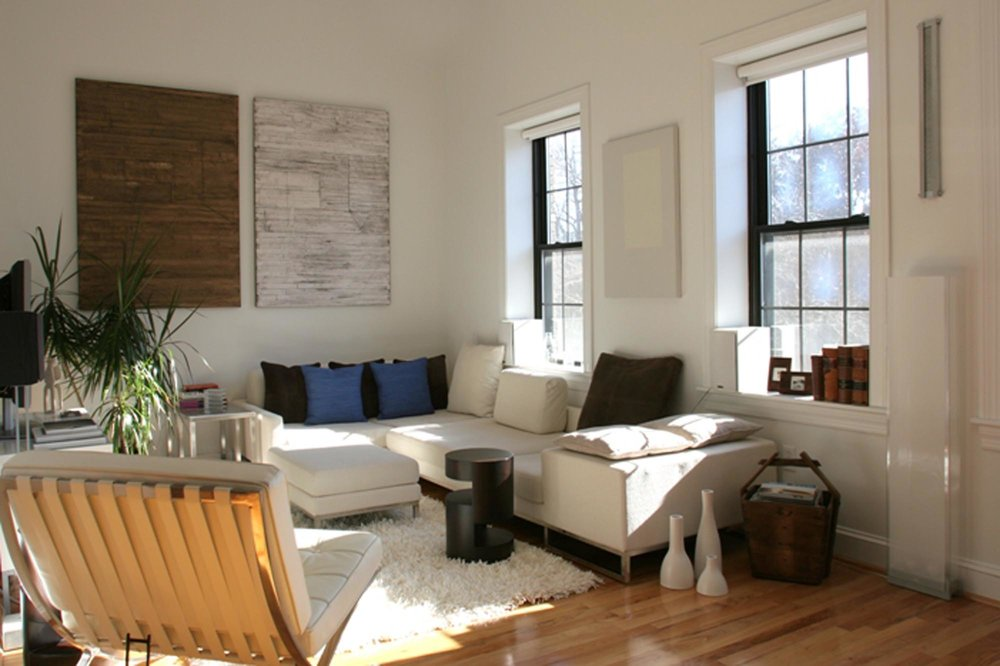 Living room with light brown sofa, white rug and other decorations on wooden flooring