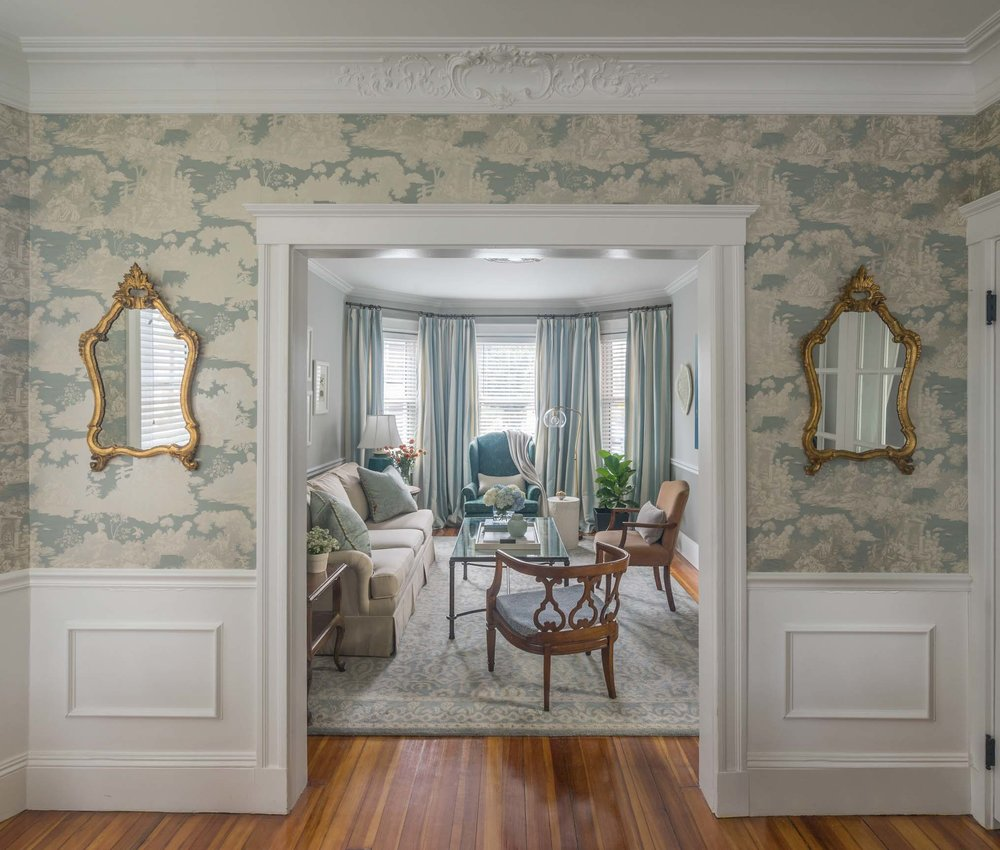 Entryway with fancy wall coverings and gold guilded mirrors.