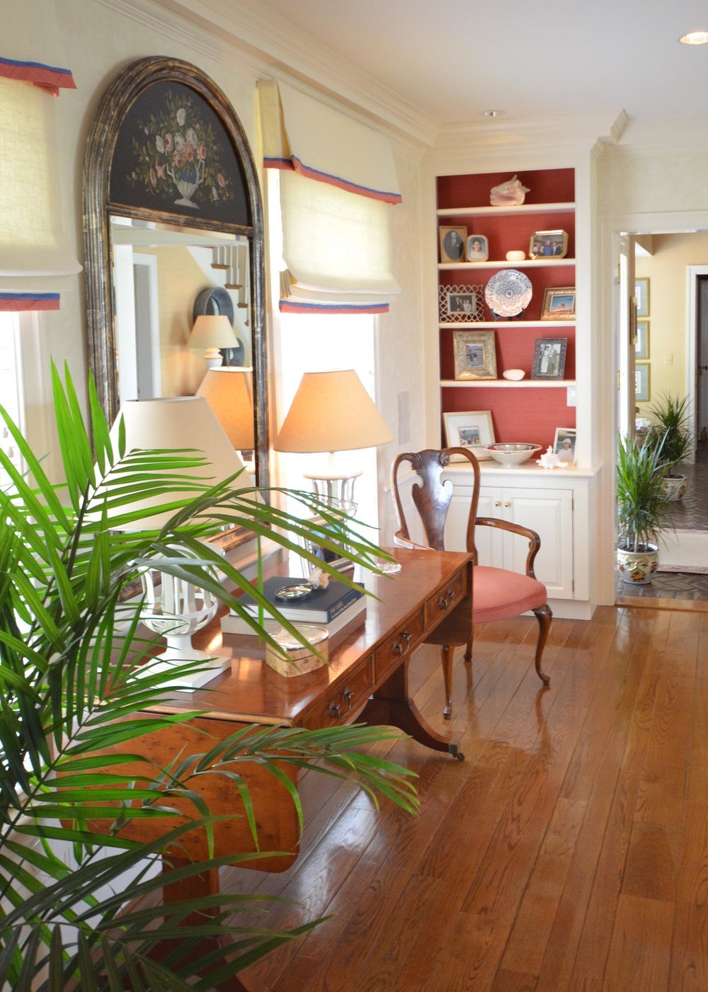 House hall with large mirror desk lamps on wooden table,bookshelves and indoor plant