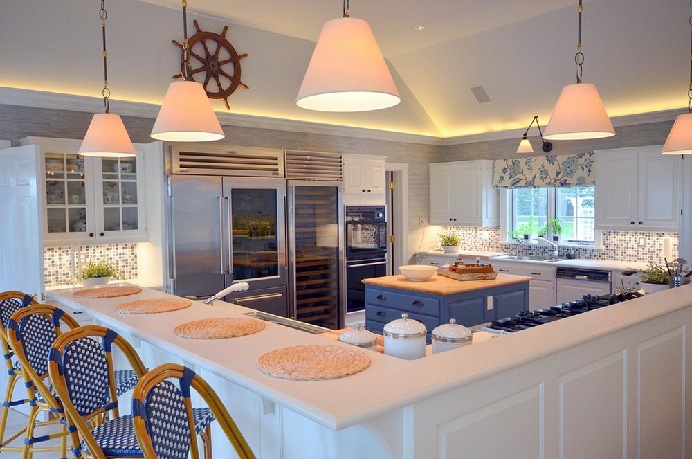 Modern kitchen Design features bar style kitchen island with white counter top and stylish ceiling lights