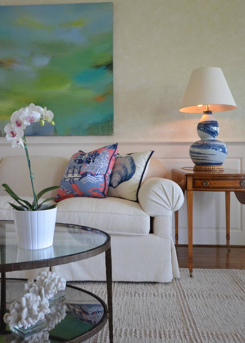 Living room sofa with pillows and flower on the glass coffee table
