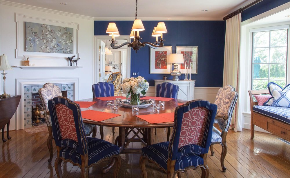 Dining Area with wooden round table for six, stylish chandelier and fireplace