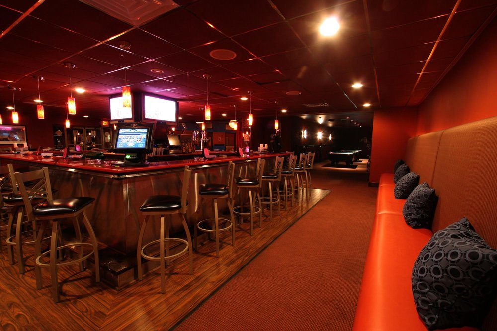 Bar area with red walls and black stools