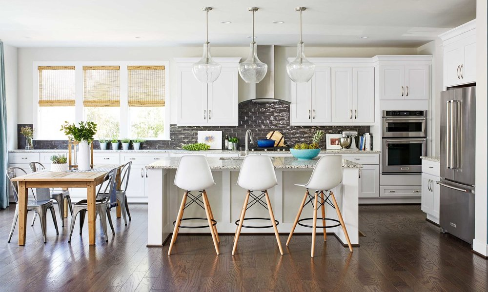 Open kitchen with white cabinets and metal backsplash